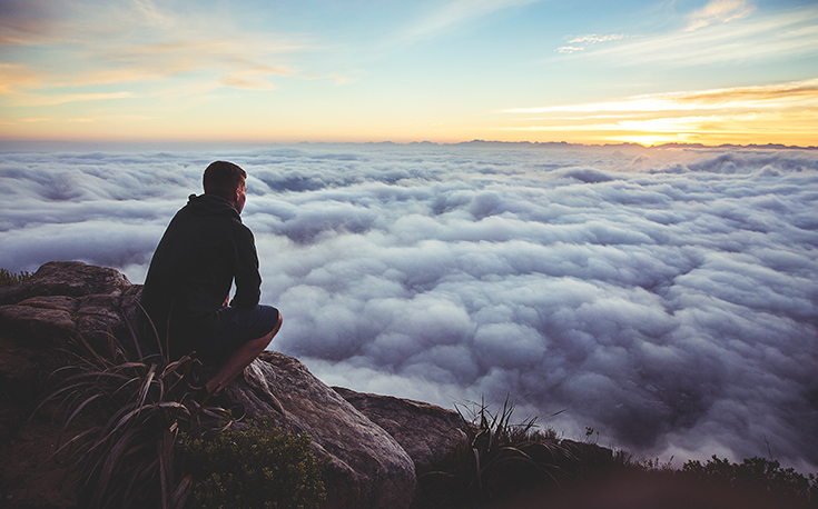 Guy Looking over Clouds on Top of Mountain